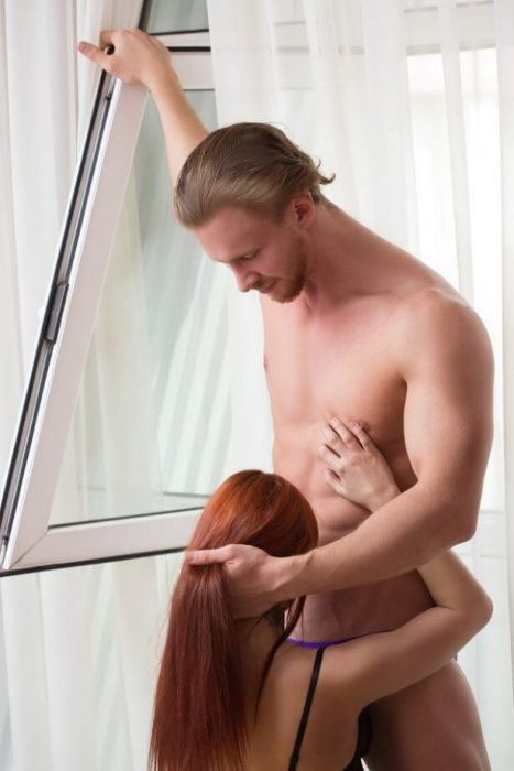 red-haired girl engaged in oral sex with a muscular guy